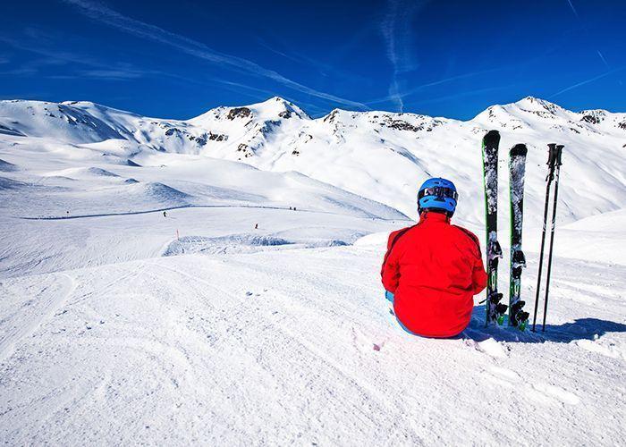 Ragazzo seduto sulla neve di Livigno con attrezzatura di Point rent a ski
