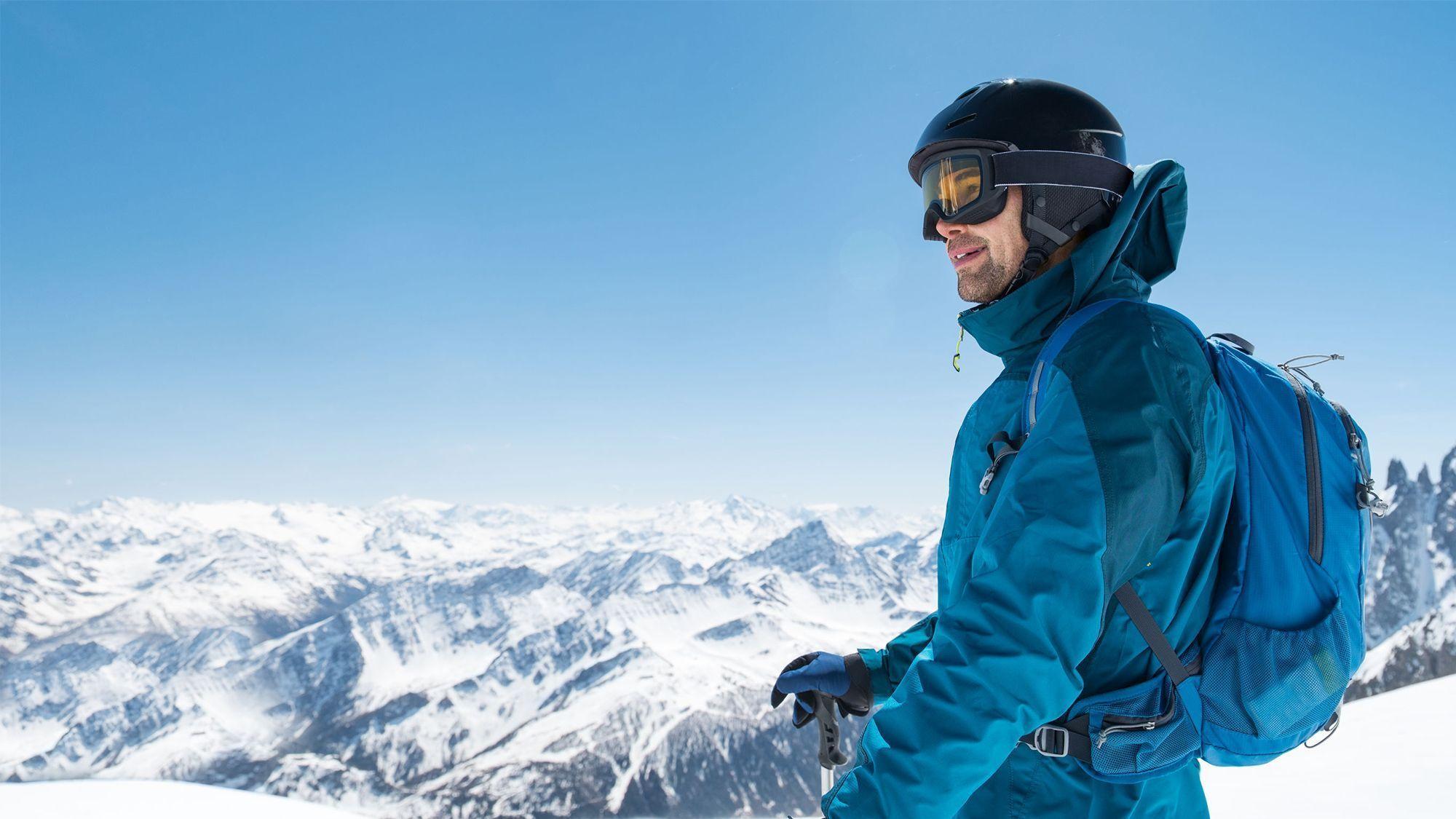 Ragazzo vestito da sci con attrezzatura di Point rent a ski che guarda il panorama di Livigno